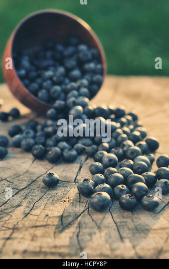 Fresh blueberries in a basket on wooden table - Stock Image