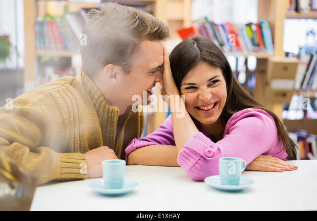 Playful young couple with coffee cups on desk in library - Stock Image