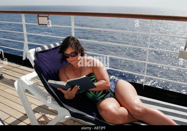 Puerto Rico Atlantic Ocean Holland America Line ms Noordam Lido Deck woman reads sunbathe lounge chair - Stock Image