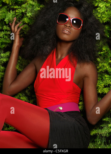 Young stylish black woman in bright red clothes and sunglasses leaning against green bushes - Stock Image