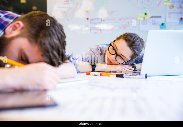 Exhausted young woman and man sleeping on the table in office - Stock Image