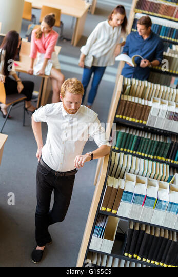 Group of young people preparing for an exame in a library and have no much time left. Deadline - Stock Image