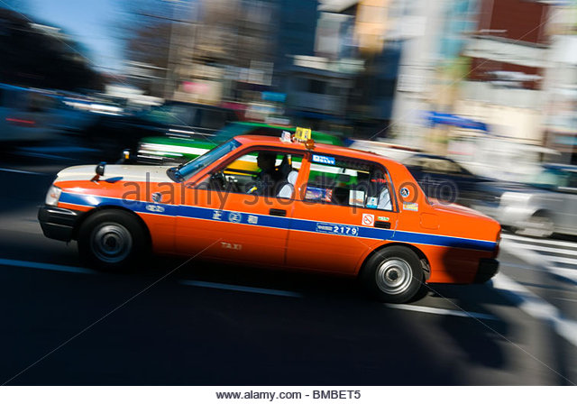 Colorful taxi in motion at street intersection, Tokyo, Japan. - Stock Image