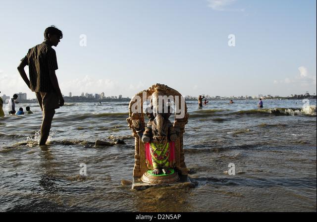 A Ganesha idol washes ashore in Mumbai, Maharashtra, India, Asia - Stock Image