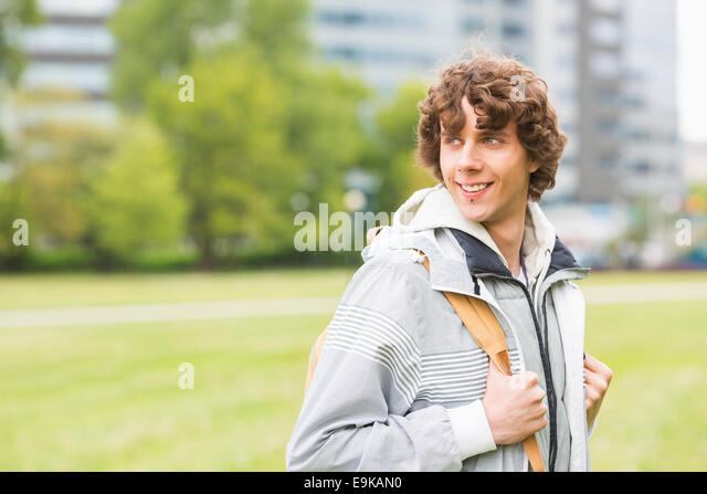 Smiling young male university student at college campus - Stock Image