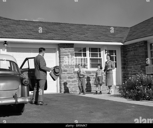 1950s FAMILY GREETING FATHER IN DRIVEWAY - Stock Image