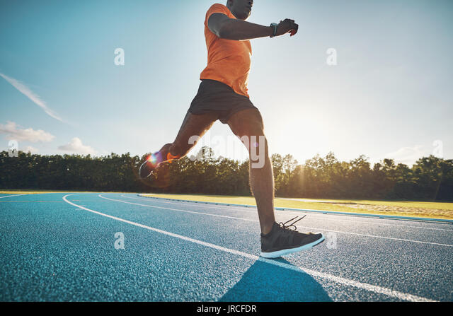 Focused young African male athlete in sportswear sprinting alone down a running track on a sunny day - Stock Image