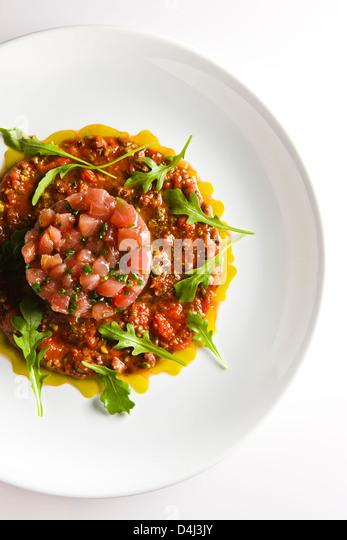 Tuna Tartare with Cold Puttanesca sauce and Baby Arugula prepared by Marcello Russodivito, Chef Owner of Marcello's - Stock Image
