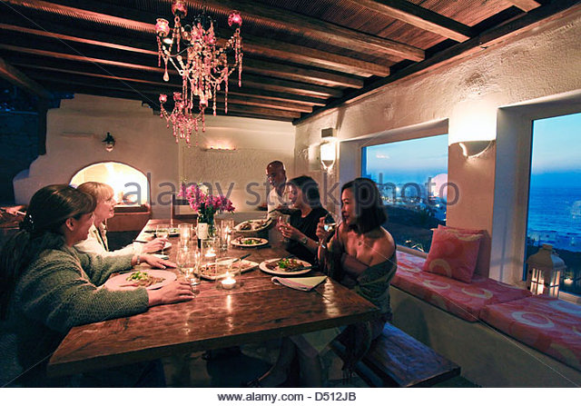 People sharing a meal at wooden dining table, Mykonos, Greece - Stock-Bilder