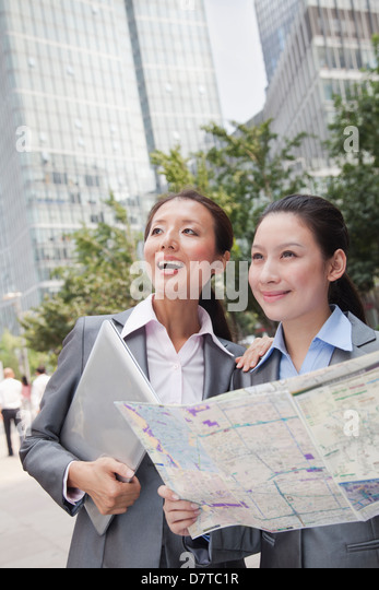 Two young businesswomen with the map looking for location - Stock Image