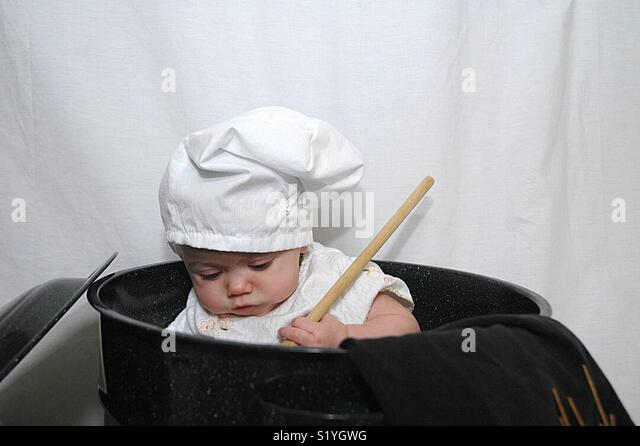 A baby plays with cooking implements. - Stock Image