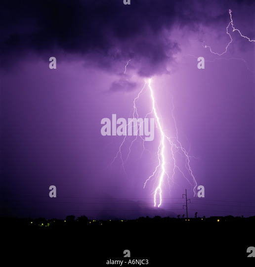 A large lightning bolt strikes down from a purple sky in the Catalina Foothills in Tucson Arizona, USA. - Stock Image