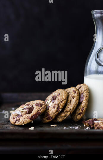 chocolate chunk cookies with oats, sea salt, and carafe of milk - Stock Image