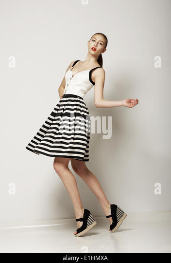Fashion Style. Happy Young Shopper in Contrast Striped Grey Skirt. Movement - Stock Image
