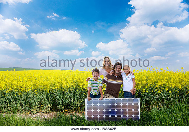 Family posing with solar panel - Stock Image