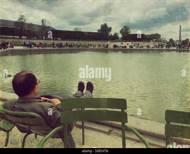 Man relaxing on a lawn chair by the Bassin Octagonal pond at Jardin des Tuileries garden in Paris, France. Vintage - Stock Image