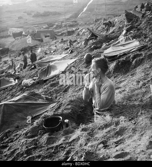 D-DAY LANDINGS 1944 - US soldier shaves in his foxhole near Cherbourg in June 1944 - Stock Image