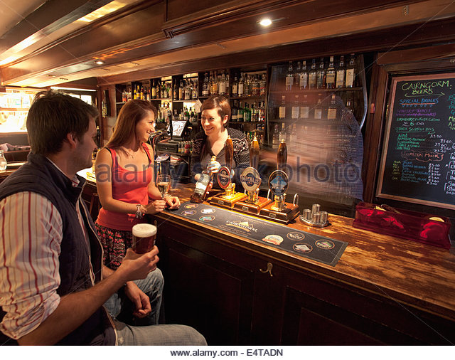 A barmaid shows a bottle of whisky to a couple enjoying a drink in the bar at the Old Bridge Inn, Aviemore, Highlands - Stock Image