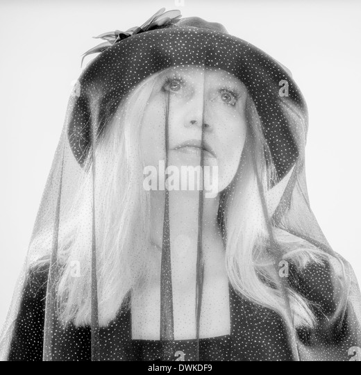 Widow, mature woman wearing black costume and veil, studio shot - Stock Image