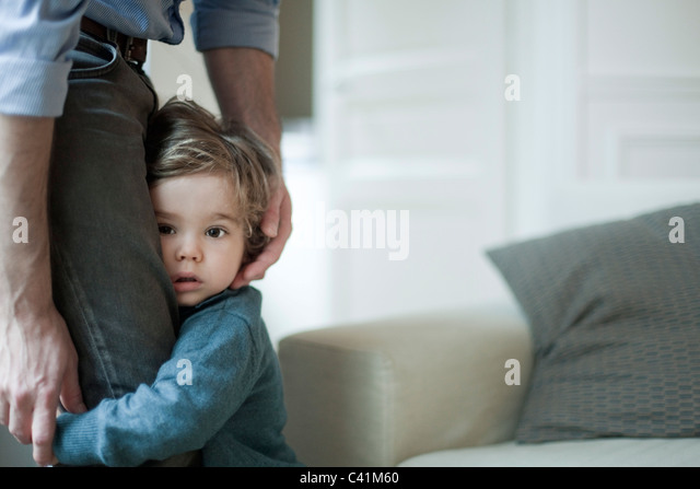 Toddler boy holding on to father's legs - Stock Image