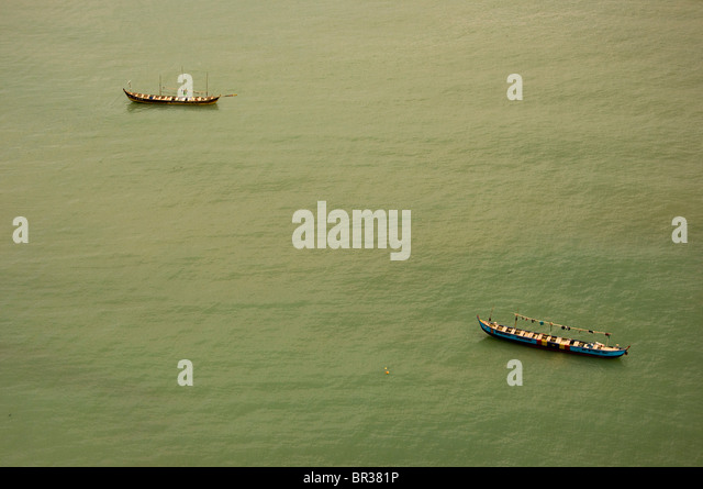 Two small traditional Ghanaian fishing boats at anchor in calm midday waters off the shore of  Cape Coast. - Stock Image