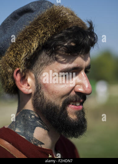 Sept. 19, 2015 - Enactors in medieval Scandinavian clothes with a crow on his neck tattoo -- In the historical festival - Stock-Bilder