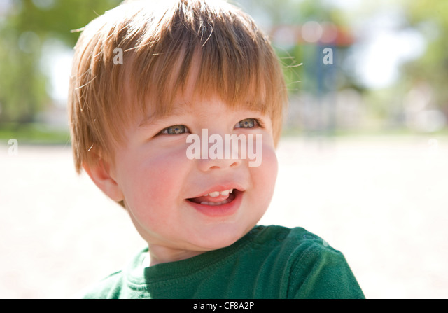 Adorable two year old boy looking happy in the sun. - Stock Image