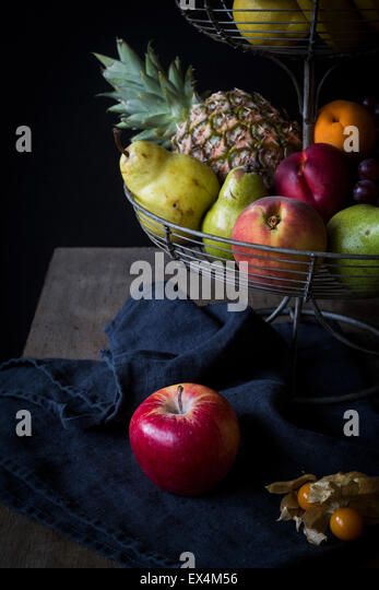 Fresh fruits in metal étagère before dark background - Stock Image
