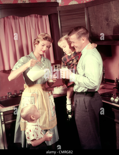 1950s FAMILY IN KITCHEN MOTHER POURING MILK  FROM PITCHER FOR DAD AND KIDS - Stock Image