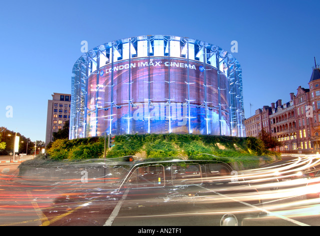 London's IMAX cinema and passing traffic at dusk. - Stock Image