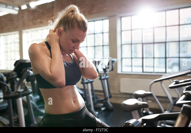 Indoor shot of young woman feeling tired after working out on stationary bikes in gym. Relaxing her neck muscles. - Stock Image