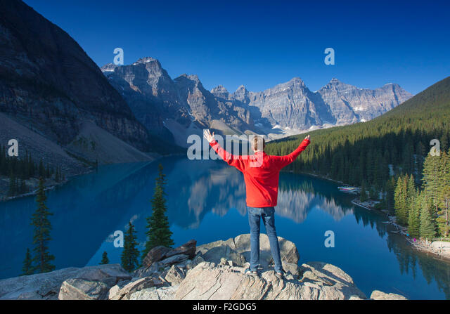 Tourist with open arms on look-out point looking over Moraine Lake in the Valley of the Ten Peaks, Banff NP Alberta, - Stock-Bilder