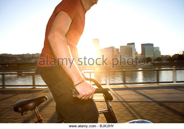 Athletic man riding bicycle on urban bridge at sunset - Stock Image
