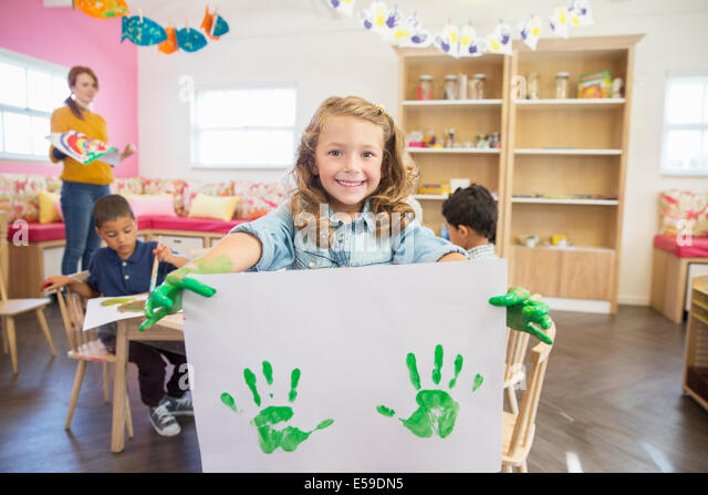 Student holding finger painting in class - Stock Image