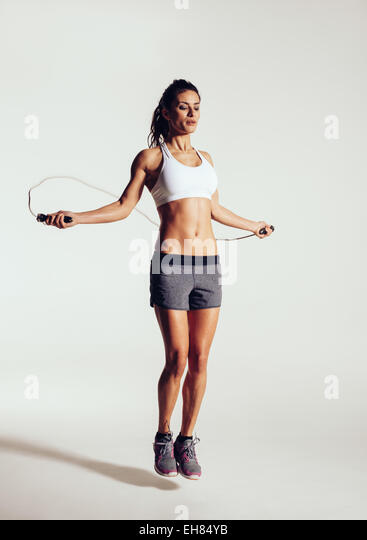 Healthy young woman skipping rope in studio. Muscular young woman exercising with jumping rope on grey background. - Stock Image