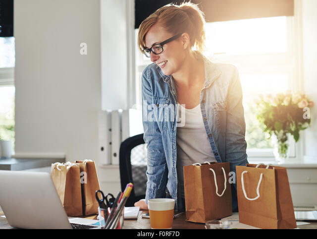 Happy businesswoman working in a home office standing looking at her laptop computer surrounded by gift bags and - Stock Image