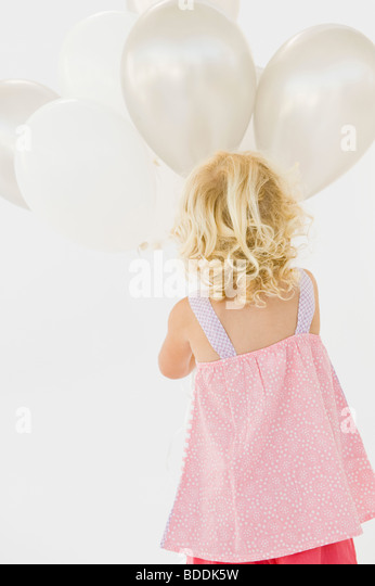 Rear view of a girl holding balloons - Stock Image