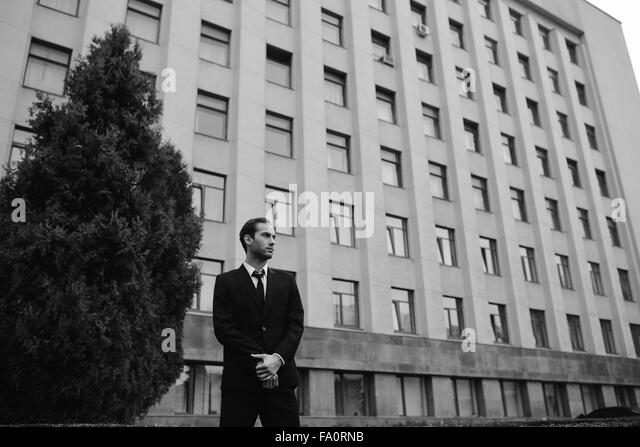 young guy in a suit posing - Stock Image