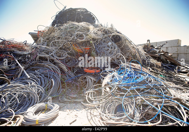 Heap of coiled and tangled cables in scrap metal yard - Stock Image