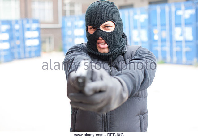 Man in ski mask holding gun - Stock Image
