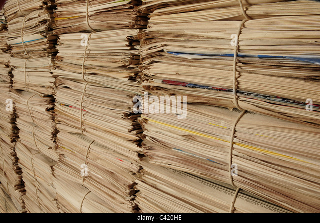 Close-up of piles of newspapers on an angle to be recycled - Stock Image