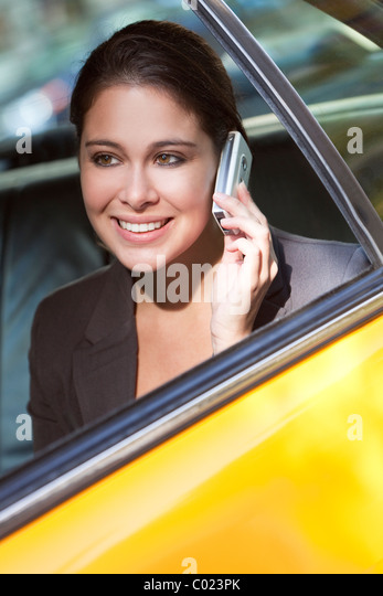 A happy young woman talking on her mobile cell phone in the back of a yellow taxi cab. Shot on location in New York - Stock Image