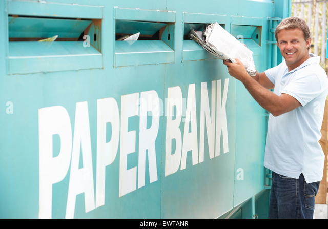 Man At Recycling Centre Disposing Of Old Newspapers - Stock Image