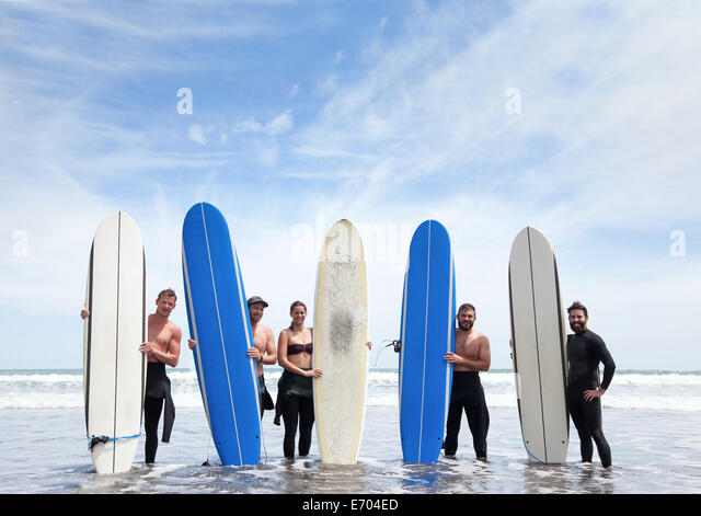 Group portrait of male and female surfer friends standing in sea with surfboards - Stock Image