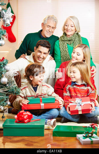 Happy family with three generations celebrating christmas with gifts - Stock Image