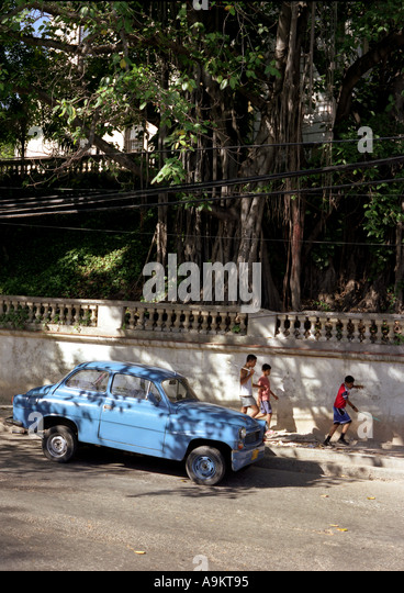 Old blue car in Havana with playing kids - Stock Image