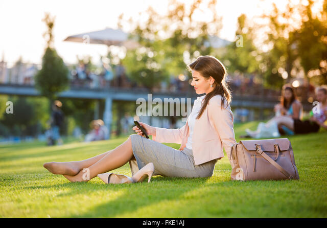Businesswoman sitting in park checking her smartphone, sunny sum - Stock Image