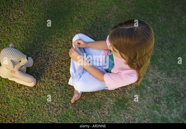 Young girl sitting on grass opposite toy bear - Stock Image