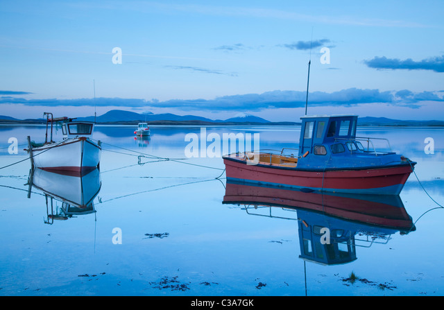 Fishing boats reflected at dusk in Clew Bay, County Mayo, Ireland. - Stock Image