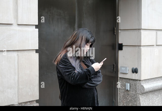 Loan woman seen having break and using her mobile phone device in a hotel archway in New York City. - Stock-Bilder